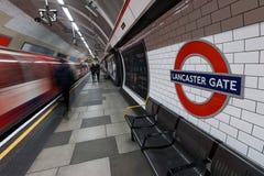 Het Ondergrondse teken van Londen met het bewegen van trein en mensen in Lancaste stock afbeeldingen