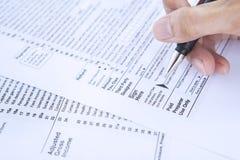 Het ondertekenen van belastingsvorm Stock Afbeeldingen