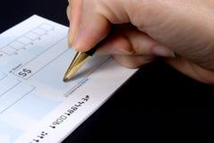 Het ondertekenen van een Cheque Stock Foto's