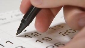 Het ondertekenen van een dag op een kalender door rood penvierkant stock video
