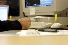 Het ondertekenen van een Document op een Slordig Bureau Stock Afbeeldingen
