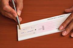 Het ondertekenen van een geldcheque Stock Foto's