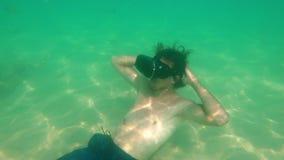 Het onderwaterschot van een jonge mens gebruikt een VR-hoofdtelefoon leggend op een overzeese bodem Een persoon die een vrglazen  stock video
