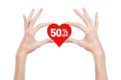 Het onderwerp van de Dagkortingen van Valentine: Hand die een kaart in de vorm van een rood hart met een korting van 50% op geïso Stock Afbeelding