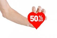 Het onderwerp van de Dagkortingen van Valentine: Hand die een kaart in de vorm van een rood hart met een korting van 50% op geïso Royalty-vrije Stock Afbeeldingen