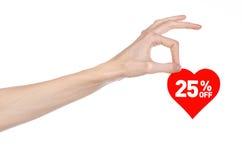 Het onderwerp van de Dagkortingen van Valentine: Hand die een kaart in de vorm van een rood hart met een korting van 25% op geïso Stock Fotografie