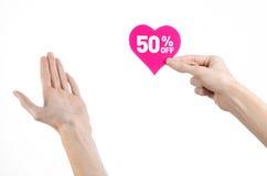 Het onderwerp van de Dagkortingen van Valentine: Hand die een kaart in de vorm van een roze hart met een korting van 50% op geïso Stock Afbeelding