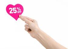 Het onderwerp van de Dagkortingen van Valentine: Hand die een kaart in de vorm van een roze hart met een korting van 25% op geïso Stock Afbeeldingen