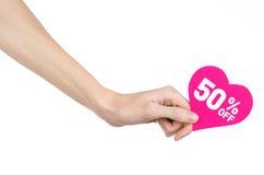 Het onderwerp van de Dagkortingen van Valentine: Hand die een kaart in de vorm van een roze hart met een korting van 50% op geïso Royalty-vrije Stock Foto