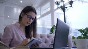 Het onderwijs in Internet, gelukkige studente in oogglazen schrijft nota's in notitieboekjezitting bij lijst met laptop apparaat stock videobeelden