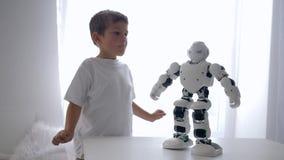 Het onderwijs leuke speelgoed, weinig jongen herhaalt bewegingen van robot met kunstmatige intelligentieclose-up in ruimte stock videobeelden