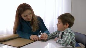 Het onderwijs van blinde kinderen, moeder onderwijst kindjongen om braille-zitting bij lijst in heldere ruimte te schrijven stock video