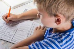 Het onderwijs van het huis Het huiswerk na school Jongen die met pen Engelse test met de hand aangaande traditioneel wit blocnote royalty-vrije stock afbeelding