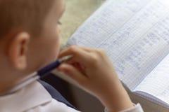 Het onderwijs van het huis Het huiswerk na school Jongen die met pen Engelse woorden met de hand op traditioneel wit blocnotedocu stock fotografie