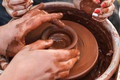 Het onderwijsaardewerk De carftman handen die van ` s een kindhand leiden, die tonen hoe te een kleipot op een pottenbakkerswiel  Stock Fotografie