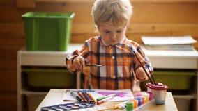Het Onderwijsconcept van de jong geitjecreativiteit, Kind het Leren Art. Kleuterjongen die pret met kleurrijke verf hebben bij ee stock footage