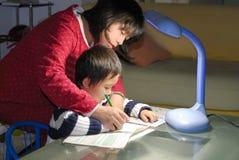 Het onderwijskind van Mum het schrijven Stock Afbeeldingen