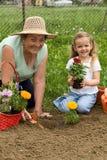 Het onderwijsmeisje van de grootmoeder het tuinieren Stock Foto's