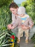 Het onderwijsplantkunde van de moeder haar jong geitje Stock Foto