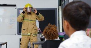 Het onderwijsschoolkinderen van de vooraanzicht Kaukasische mannelijke brandbestrijder over brandveiligheid in het klaslokaal 4k stock videobeelden