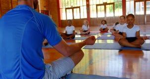 Het onderwijsyoga van de yogainstructeur aan schooljonge geitjes in school 4k stock footage