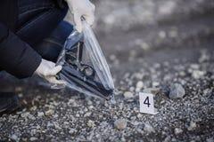 Het onderzoek die van de misdaadscène - pistool op manier verzamelen royalty-vrije stock afbeelding