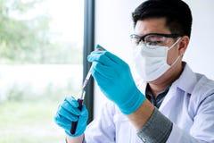 Het onderzoek van het biochemielaboratorium, Chemicus analyseert binnen steekproef stock foto