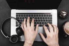 Het onderzoek van internetgebruiker` s handen naar een favoriet lied, laptop, hoofdtelefoons royalty-vrije stock foto
