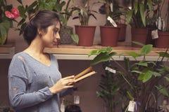 Het onderzoek van studentenWoman over bloemen stock afbeelding