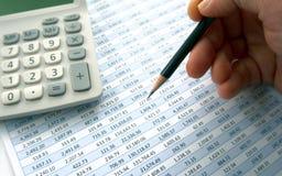 Het onderzoeken van spreadsheet met calculator stock foto