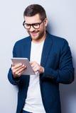 Het onderzoeken van zijn gloednieuwe tablet Stock Afbeelding