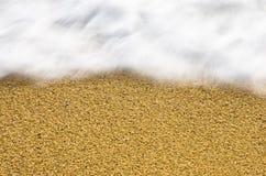 Het onduidelijke beeld van de golfmotie en scherp zand op een strand bij klein Grieks dorp Stock Foto's