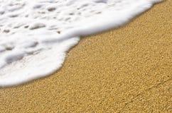 Het onduidelijke beeld van de golfmotie en scherp zand op een strand bij klein Grieks dorp Stock Afbeeldingen