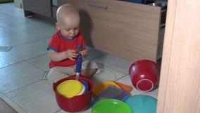 Het ongehoorzame kind spelen met kommen op keukenvloer stock footage