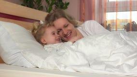 Het ongehoorzame lachende meisje ligt dichtbij haar moeder in bed stock videobeelden
