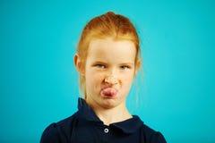 Het ongehoorzame roodharigemeisje toont tong en plaagt u, close-upportret op blauw geïsoleerde achtergrond stock foto
