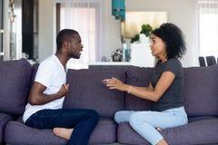 Het ongelukkige Afrikaanse Amerikaanse paar ruzie maken, die op bank thuis zitten stock afbeeldingen