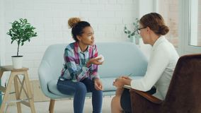 Het ongelukkige gemengde rasmeisje spreekt aan psycholoog en schreeuwende zitting op laag terwijl de arts aan haar holding luiste stock video
