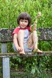 Het ongelukkige jong geitje spelen alleen met klimopbladeren die naakte voet krassen royalty-vrije stock foto