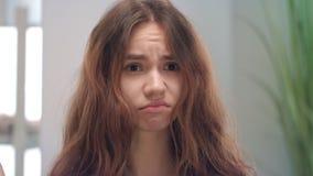 Het ongelukkige jonge vrouw betrekking hebben en het kijken op droog haar be?indigen in spiegel bij badruimte stock footage