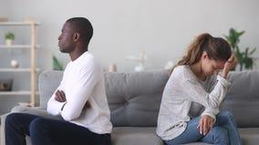 Het ongelukkige koppige gemengde het behoren tot een bepaald ras jonge paar zit afzonderlijk op bank stock videobeelden