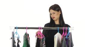 Het ongelukkige meisje kiest kleding in de winkel wit stock video