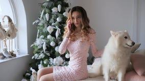 Het ongelukkige meisje met mobiele telefoon zit dichtbij op bed aan witte hond op vooravond van Kerstmis stock video