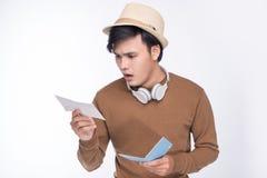 Het ongerust gemaakte Aziatische mannelijke paspoort van de toeristenholding over grijze achtergrond stock foto's