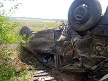Het ongeval van de auto De gebroken omgekeerde auto ligt dichtbij weg Royalty-vrije Stock Foto's