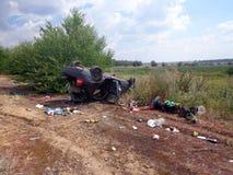Het ongeval van de auto De gebroken omgekeerde auto ligt dichtbij weg Royalty-vrije Stock Afbeeldingen