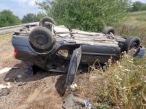 Het ongeval van de auto De gebroken omgekeerde auto ligt dichtbij weg Stock Fotografie