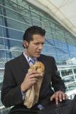 Het Ongezuurde broodje van zakenmanwith laptop eating royalty-vrije stock foto