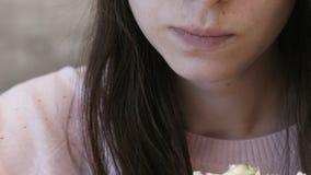 Het onherkenbare jonge donkerbruine vrouw danar eten of Shawarma-zitting in een koffie met Frieten stock video