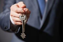 Het onherkenbare zakenman aanbieden sleutels Stock Foto's